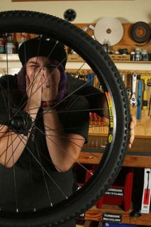 Gabby laughing behind a bike wheel.